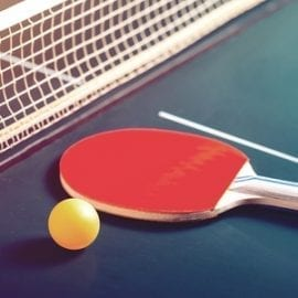 able Tennis Rackets and Ball on Table with Net